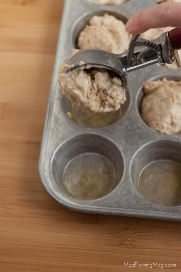 image of scoop of batter in muffin tin