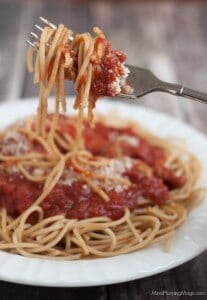 homemade spaghetti sauce and pasta wrapped on a silver fork with extra on plate