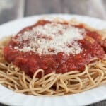 Side view image of homemade spaghetti sauce on pasta on a white plate.