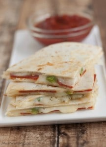 Stack of triangle shaped Pizza Quesadillas on a plate with marinara sauce in a bowl.