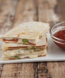 Stack of triangle shaped pizza quesadillas on a white plate with marinara sauce in small bowl.
