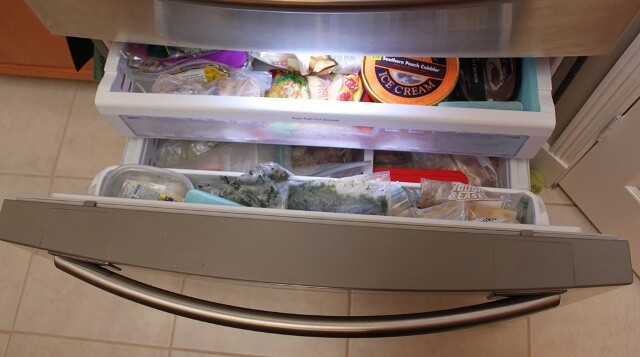 This is my freezer below the refrigerator. It may not look super organized but it is! On the upper level is baked goods like tortillas and bagels, on the right is our ice cream stash. On the bottom, left side is nuts and some other leftover recipe ingredients. On the right is frozen fruit & veggies. In the upper edge, I have frozen herbs like parsley, cilantro, garlic, ginger, etc. and some homemade coffee creamer. I use my extra freezer to hold bigger items like meat or prepared meals ready to heat and eat.[/