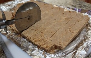 slicing pieces of peanut butter fudge with a pizza cutter