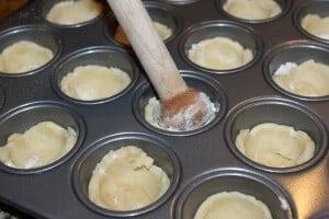 placing pecan tassies cookie dough into a tart pan