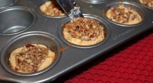 Pecan tassies being removed from the baking pan