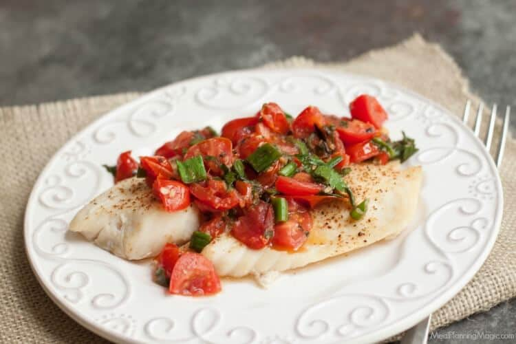 Super Simple Tomato Basil Topped Baked Fish tastes delicious and is budget friendly too! Get the recipe at MealPlanningMagic.com