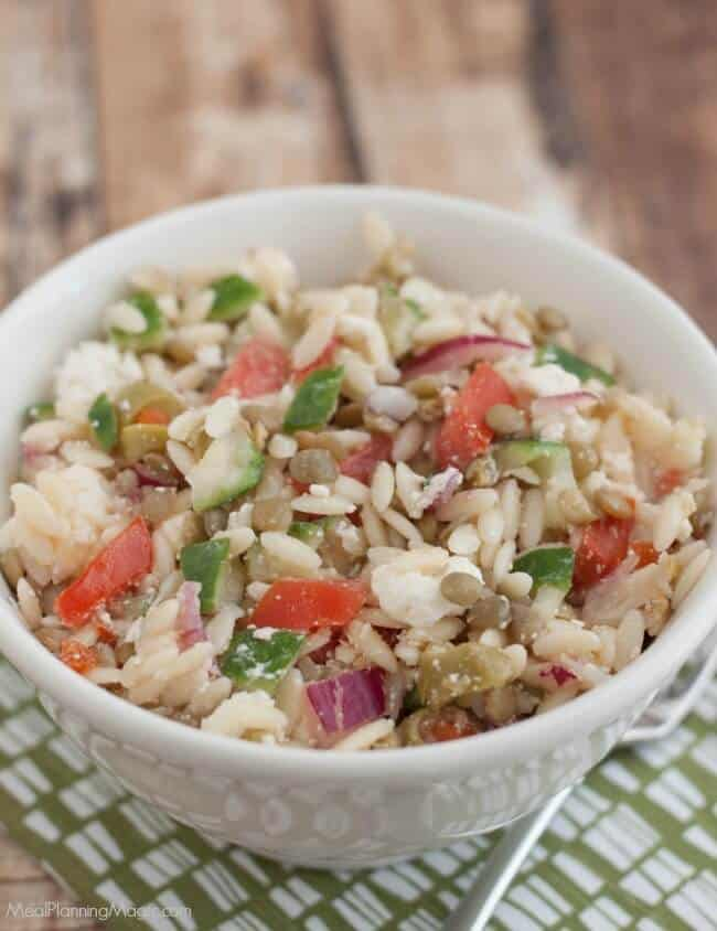 This Greek Lentil Orzo Salad a nutritious and economical way to enjoy fresh vegetables and lentils. It's make ahead too! Recipe at MealPlanningMagic.com