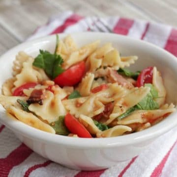 One Pot BLT Pasta in a white bowl on top of striped dish towel.