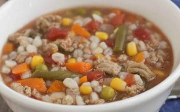 image of slowcooker ground turkey, mixed vegetable and barley soup in a white bowl on blue napkin with spoon.