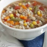 close up image of ground turkey, mixed vegetable and barley soup in a white bowl on a white plate with blue napkin.