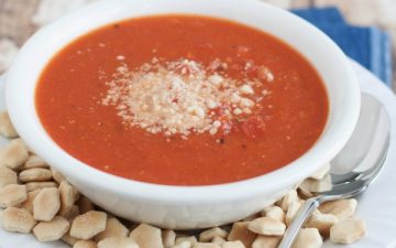 Side view image of Easy Homemade Tomato Basil Parmesan soup in white bowl with oyster crackers and spoon on blue fabric.