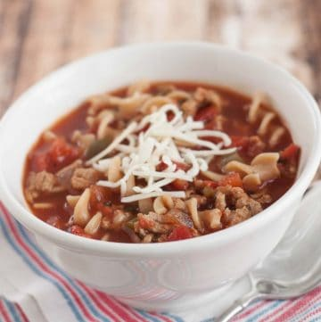 Crockpot Lasagna Soup with shredded cheese on top in a white bowl on a blue and white napkin