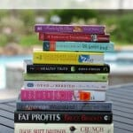 Stack of books on a table outside with text overlay at top.
