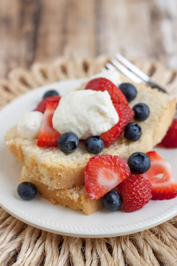 Image of Wonderful Lightened Up Pound Cake With strawberries, blueberries and cream layered on a plate and straw place mat.