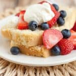 Image of Wonderful Lightened Up Pound Cake with Berries and Cream layered on a plate and a straw place mat.