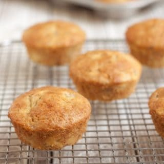 Image of banana muffins placed on a cooling rack with muffin tin in background.