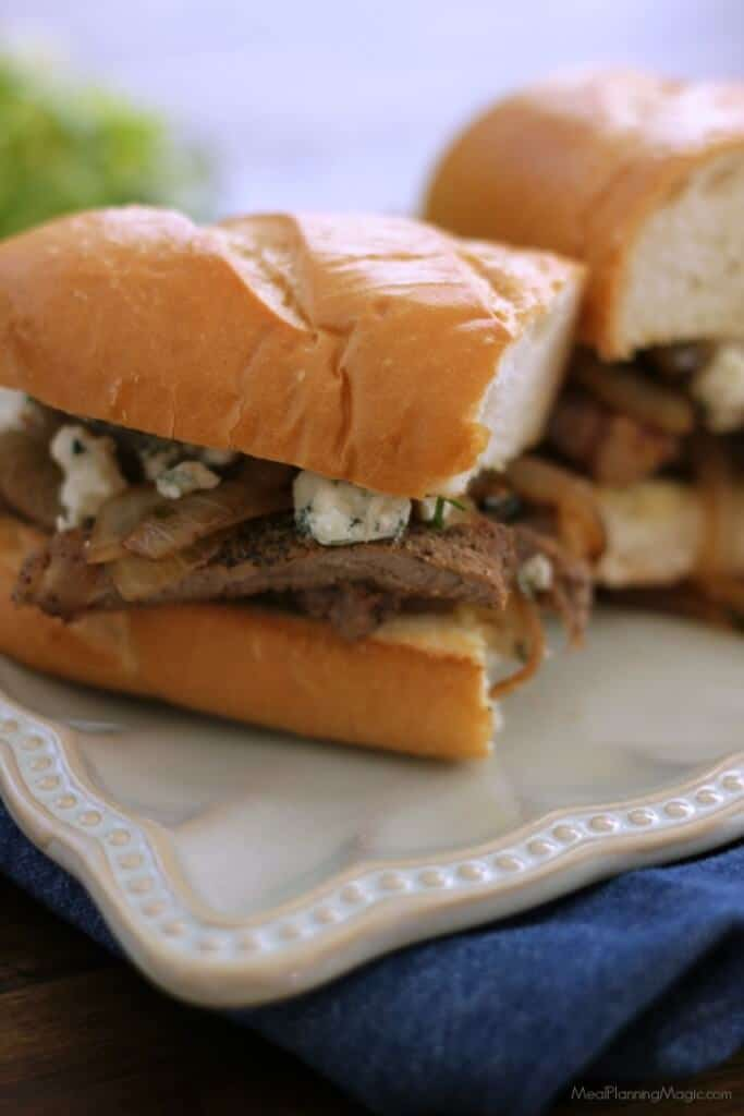 Two halves of a steak and onion sandwich with blue cheese on a hoagie bun on a white plate on a blue napkin.