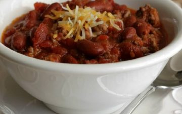 Slowcooker Classic American Chili with beans topped with grated cheddar cheese in a white bowl on a white plate with spoon on side.