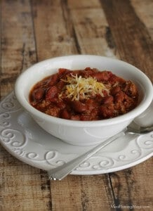 side view image of slowcooker classic American chili with beans topped with shredded cheddar cheese in a white bowl on a white plate