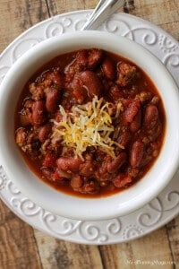 top view image of slowcooker classic American chili with beans topped with shredded cheddar cheese in a white bowl on a white plate