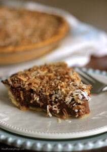Side view of slice of German Chocolate Sweet Cream pie on white plate on blue plate with whole pie in background.