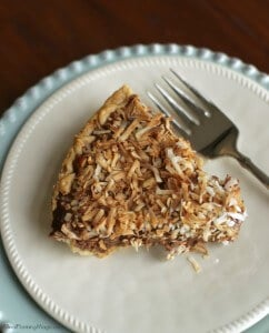 Top view of slice of German chocolate sweet cream pie on a white plate on blue plate charger with fork.