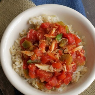 Top view image of seafood and tomato creole on steamed rice in a white bowl on a brown and blue napkin
