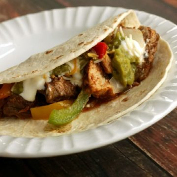 image of Simple Slowcooker Steak and Chicken Fajitas and bell peppers and onions in a tortilla