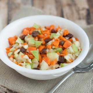 Chopped carrots and apples with raisins in a white bowl on burlap napkin.