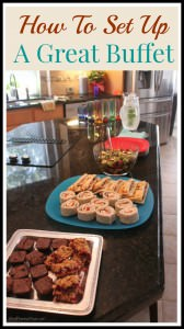 Buffet of different food on platters on a black counter in a kitchen.