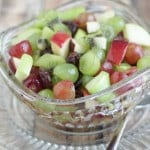 Glass bowl with fruit salad filled with red and green grapes, red and green apples and dried cherries.