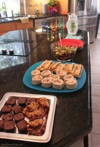 Different food on platters on a black counter in a kitchen.