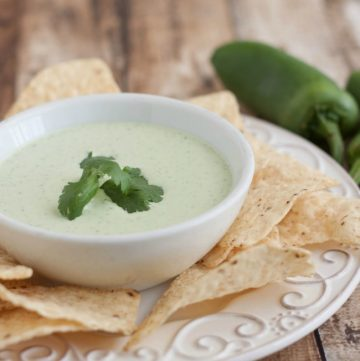Creamy Jalapeno Ranch Dip in a white bowl with sprig of cilantro on top and tortilla chips and large jalapeno on side.