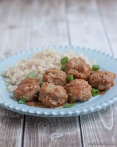 Side view image of stack of peachy ground turkey meatballs with minced green onions as garnish and rice pilaf on a blue plate.