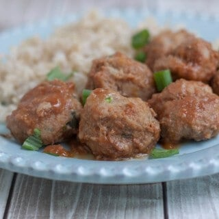 Closeup view of several peachy ground turkey meatballs with minced green onion garnish and rice pilaf on a blue plate.