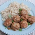 Top view image of stack of peachy ground turkey meatballs with minced green onions as garnish and rice pilaf on a blue plate.