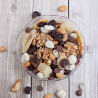 Banana Split Trail Mix is full of protein and nutrient rich nuts and dried fruit like banana chips, pineapple, cherries and just a touch of chocolate for a healthier treat on the go! Recipe at MealPlanningMagic. com