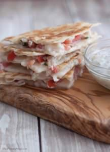 Stack of Mediterranean Chicken Quesadillas on wooden cutting board with yogurt dip on side.