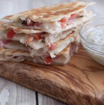 Stack of Mediterranean Chicken Quesadillas on wooden cutting board with yogurt dip on side.