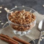 Slow Cooker Honey Cinnamon Granola in a clear bowl on a burlap napkin with cinnamon sticks and spoon on side