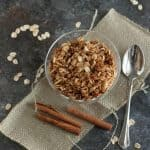 Top view image of Slow Cooker Honey Cinnamon Granola in a clear dish on a burlap napkin with cinnamon sticks and spoon on side