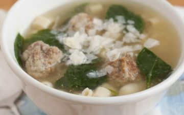 Mini meatball soup with pasta and spinach topped with Parmesan cheese in a white bowl on floral towel.