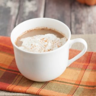 Close up image of Pumpkin Spice Latte Creamer in mug with orange checkered fabric and pumpkins.