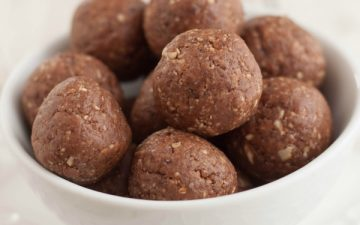 Close up image of Peanut Butter Chocolate Energy Bites in bowl on plate.