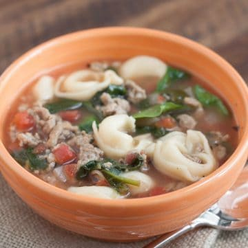 Close up image of Rustic Italian Sausage Tortellini Soup in an orange bowl.