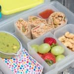 Image of bento lunchbox with (clockwise from top right) burrito bites, cashews, grapes and strawberries, colorful napkin and guacamole.