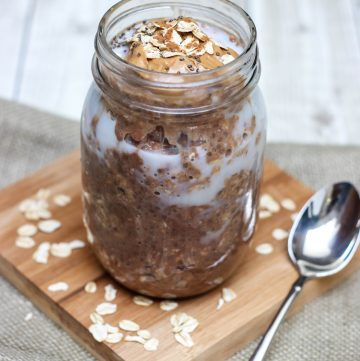 Glass jar containing ingredients mixture of Cinnamon Chocolate Peanut Butter Overnight Oats.