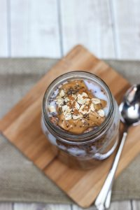 Top view of Cinnamon Chocolate Peanut Butter Overnight Oats in glass jar with peanut butter, oats and chia seeds on top.