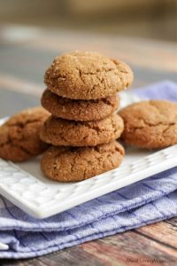 Stack of soft and chewy molasses ginger cookies on a white plate on top of a blue napkin.