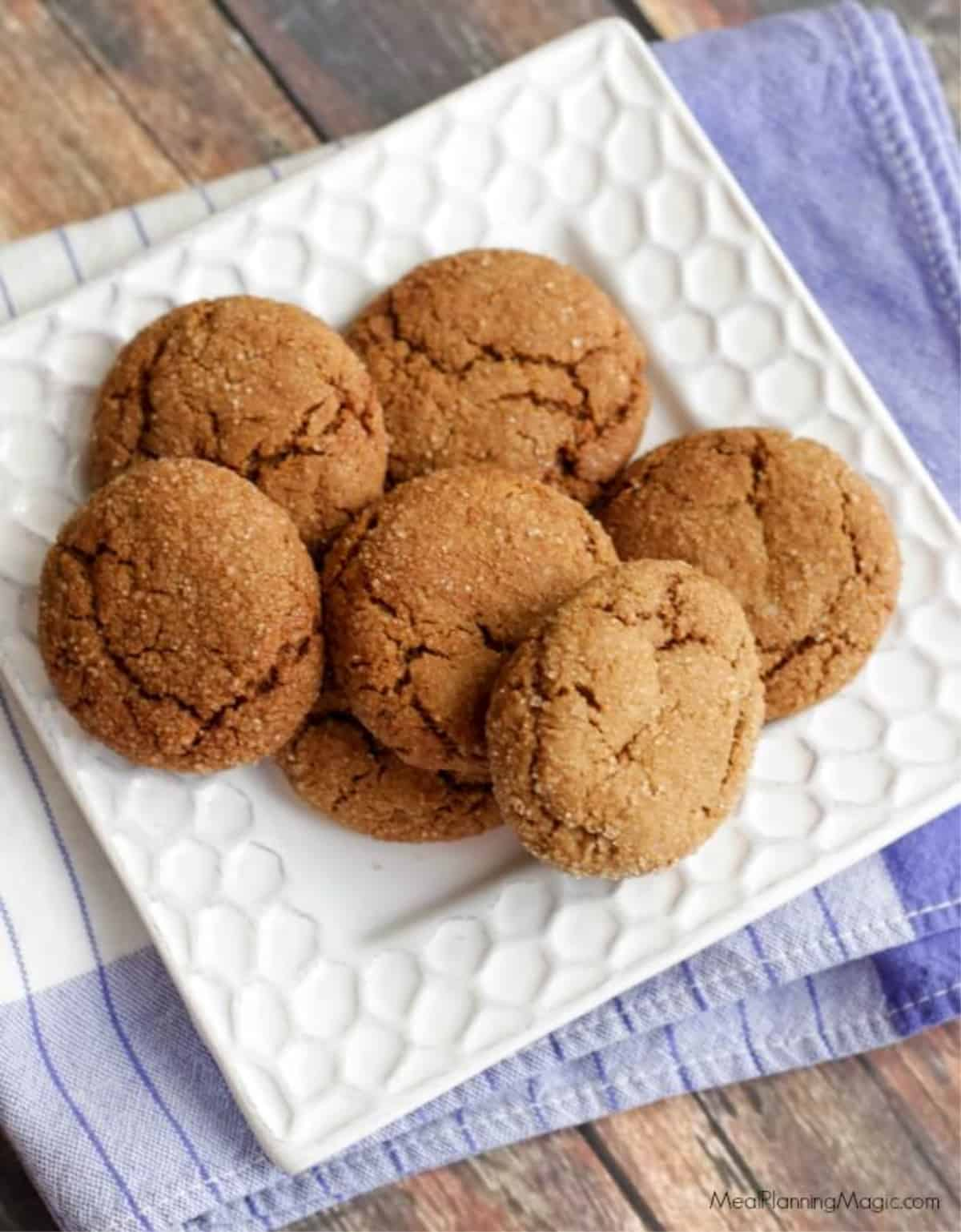Pile of soft and chewy molasses ginger cookies on a square white plate on top of a blue napkin.